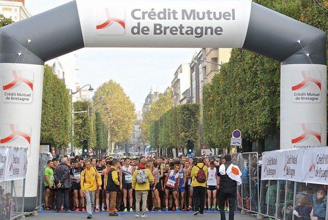 Une arche aux couleurs du Crédit Mutuel de Bretagne surplombe la foule de coureurs attendant le départ